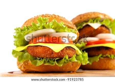 hamburger with fish cutlet and vegetables on wooden board on white background - stock photo