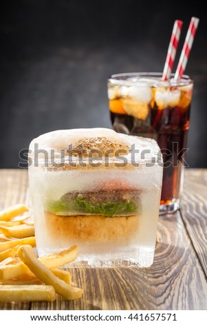Hamburger with french fries and glass of cola on wooden table - stock photo
