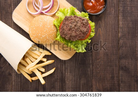 hamburger with french fries on wooden background. - stock photo
