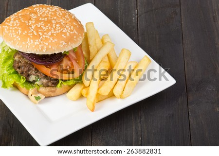 Hamburger with fresh lettuce, tomato and fries on wooden table - stock photo