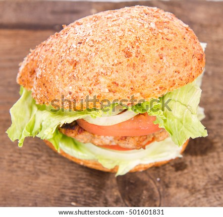 Hamburger with fresh onion, tomatoes, iceberg lettuce on a wooden board