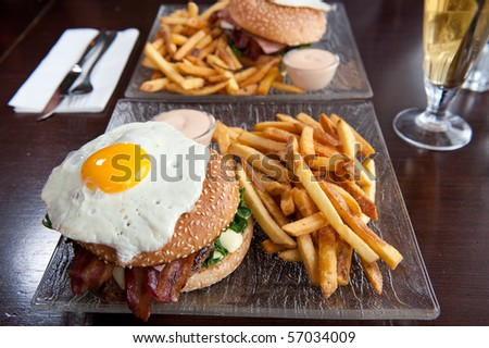 hamburger with fried egg on top and fries - stock photo