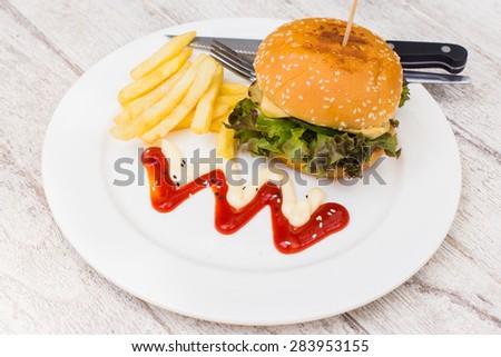 hamburger with fries and salad. - stock photo