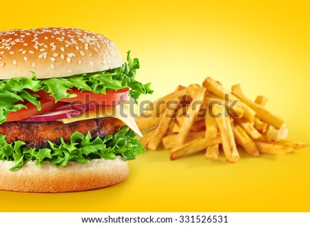 Hamburger with fries on a yellow background. Close up.