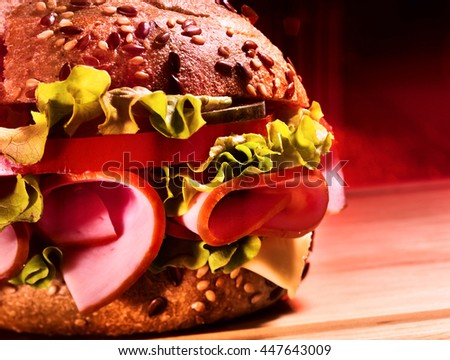 Hamburger with ham on wooden board. Half of Hamburger fast food.
