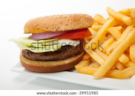 Hamburger with red onion, tomato and lettuce on a sesame seed bun with french fries on a white plate