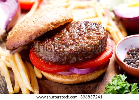 hamburger with vegetables and fries on a wooden board