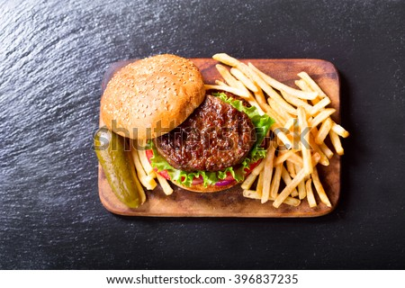hamburger with vegetables and fries on a wooden board, top view. - stock photo