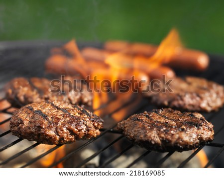 hamburgers and hotdogs cooking on grill outdoors - stock photo