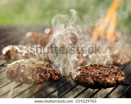 hamburgers and hotdogs with smoke and flames on grill - stock photo