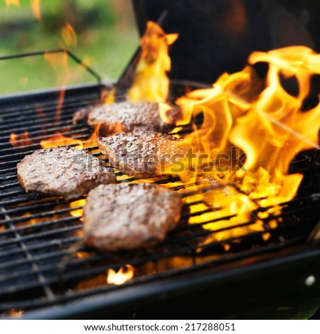 hamburgers being grilled with flames - stock photo