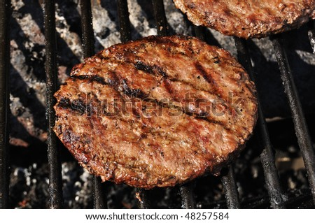 Hamburgers cooking on the grill, copy space - stock photo
