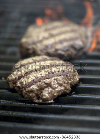 Hamburgers sizzling on the grill with flames - stock photo