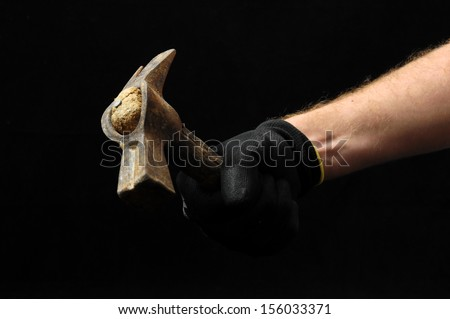 Hammer and a Hand on a Black Background - stock photo
