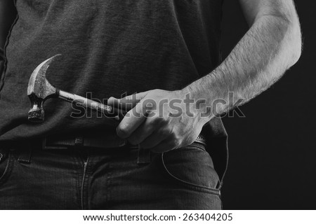 Hammer and a Hand on a Black Background in black and white.