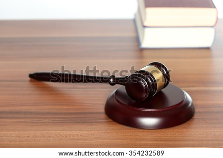 hammer and book on a wooden desk - stock photo