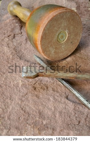 Hammer and chisel lying on a sandstone - stock photo