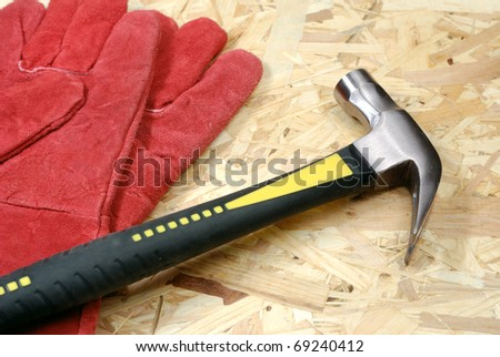 Hammer and gloves over plywood - stock photo