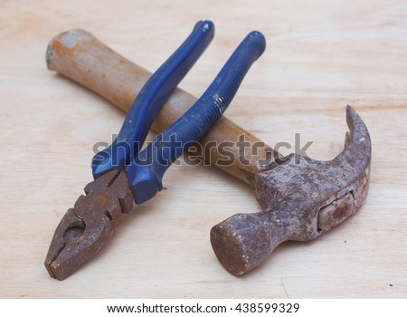 hammer and pliers on wood background - stock photo
