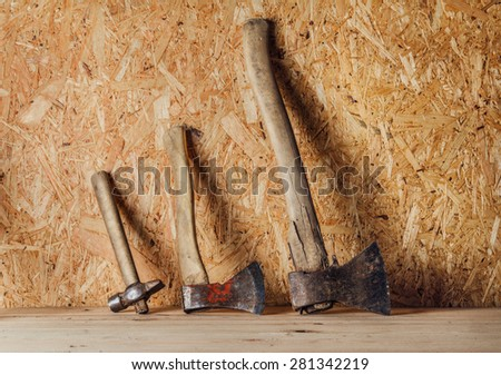 Hammer and two axes on the wooden background - stock photo