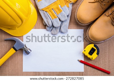 hammer helmet gloves boots tapeline pencil white blak paper on wooden board organized copyspace   - stock photo