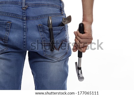 Hammer in hand and Extreme Close up of several tools in a man's rear denim pocket on the white-studio shot