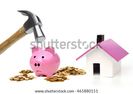 Hammer is about to hit a pink piggy bank in order to buy a house / Thinking of buying a new house - saving money for future concept