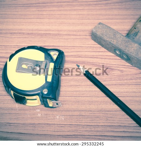 hammer measuring tape and pencil concept tools on wood background vintage style - stock photo