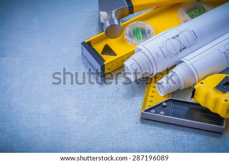 Hammer measuring tape blueprints construction level square ruler on industrial metallic background maintenance concept.