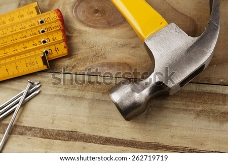 Hammer, nails and folding ruler on wood - stock photo
