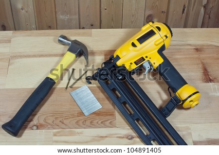 hammer,nails,and nail gun on wood background - stock photo