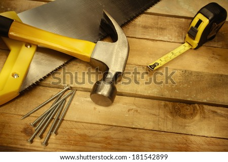 Hammer, nails, tape measure and saw on wood - stock photo