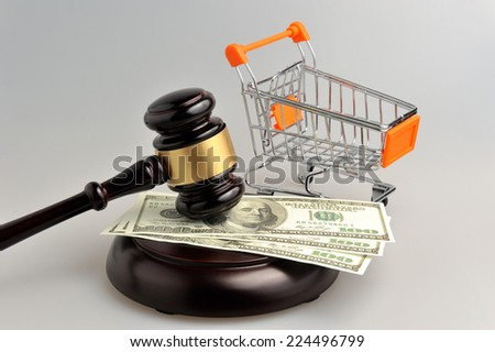 Hammer of auctioneer with pushcart and money on gray background - stock photo