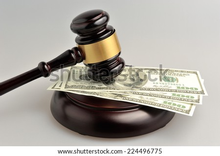 Hammer of judge with money on gray background