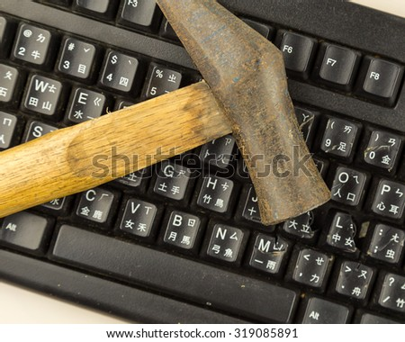 Hammer on computer keyboard with damaged keys