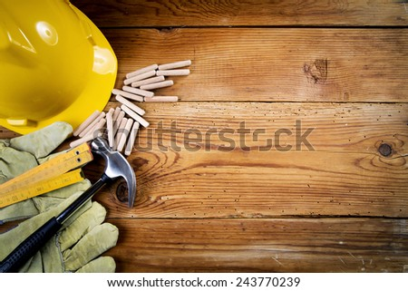 hammer, protective gloves, wooden dowels   and yellow safety helmet on wooden background