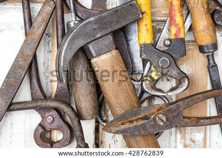 Hammer, screwdriver, wrench, chisel, tape measure and other  workshop tools. Vintage set of hand tools on a old wooden background - stock photo