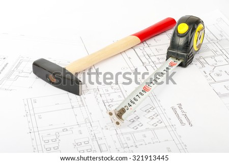 Hammer with tape measure on draft background, close up view