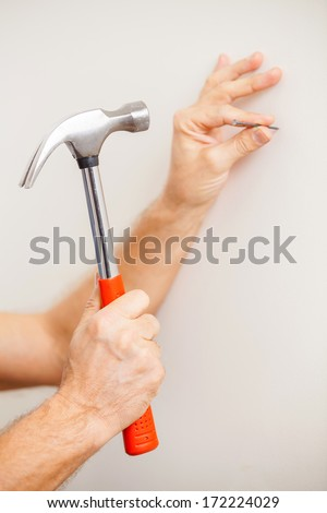 Hammering a nail. Close-up of man hammering a nail