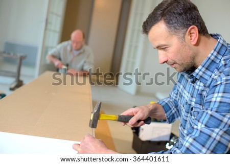 Hammering a nail into wood - stock photo