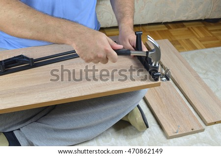 Hammering a plastic part on a drawer of a shoe cabinet