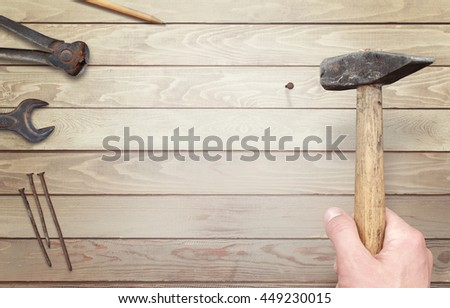 Hammering nail  in wooden surface. Pliers, pen, wrench and nails beside.