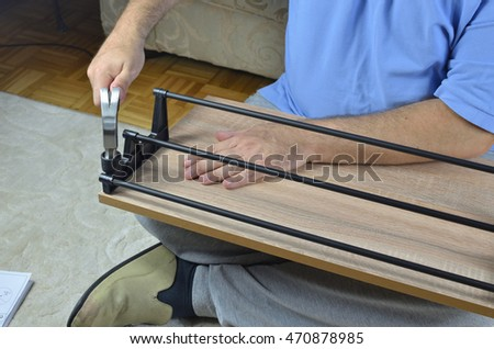 Hammering plastic holders on a drawer of a shoe cabinet