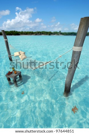 Hammock hanging over tropical sea water, and a table with refreshments