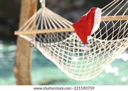Hammock in a tropical beach on christmas holidays with the clean water of the sea in the background - stock photo