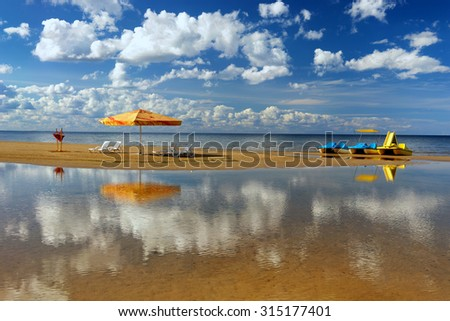 Hammock with an umbrella and chairs on a narrow strip of beach with beautiful reflection of the clouds in the Baltic Sea - stock photo