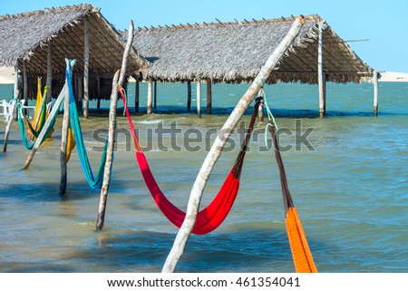 Hammocks and beach chairs under the shade of a palapa sun roof umbrella in Jericoacoara, Brazil
