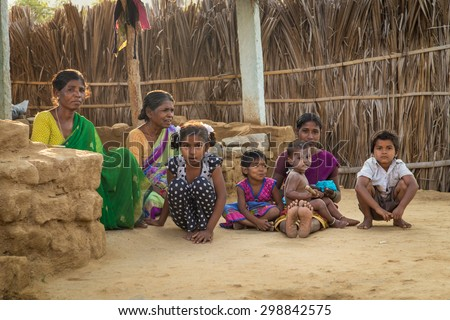 HAMPI, INDIA - 31 JANUARY 2015: Rural indian family sitting on ground in evening shade in home courtyard. - stock photo