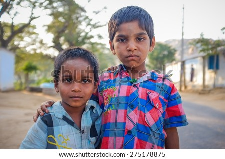 HAMPI, INDIA - 31 JANUARY 2015: Two Indian boys hugging in street - stock photo