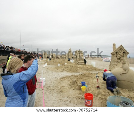 HAMPTON BEACH, NH, USA - JUNE 28: Crowds admire sand sculptures on display at the Master Sand Sculpting Competition on June 28, 2011 in Hampton Beach, NH, USA - stock photo